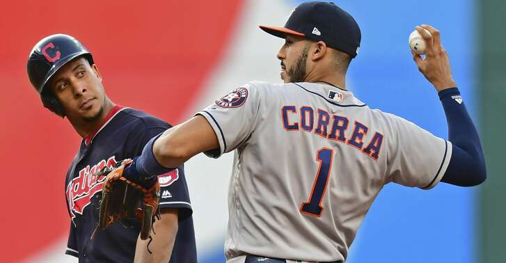 Cleveland Indians' Michael Brantley looks over at Houston Astros' Carlos Correa after Brantley hit a double during the third inning of a baseball game Friday, May 25, 2018, in Cleveland. (AP Photo/David Dermer)