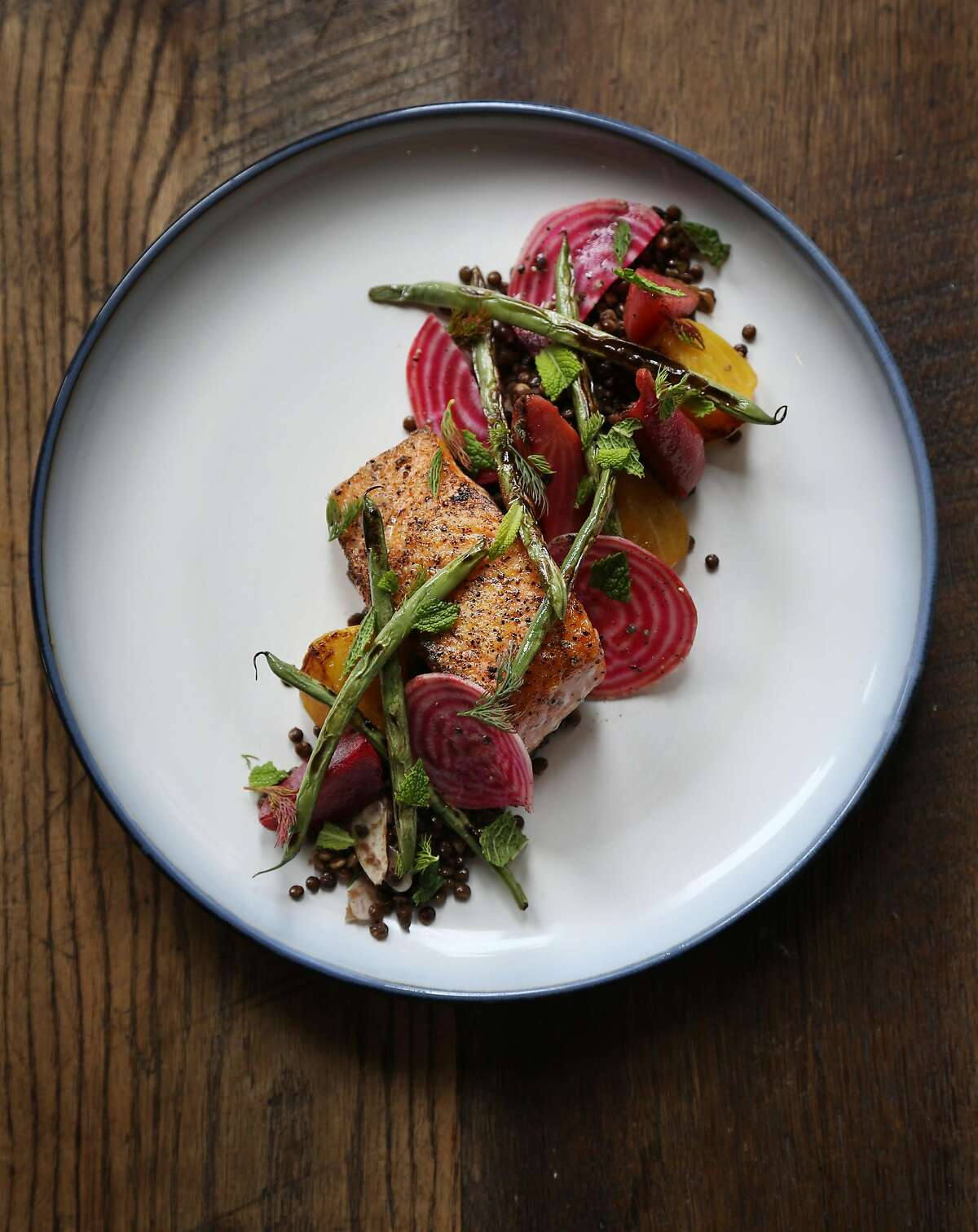 Line Caught King Salmon with roasted beets, black lentils and blistered pole beans is one of the entrees offered at Salt Wood Kitchen & Oysterette on Monday, May 21st, 2018, in Marina, California.