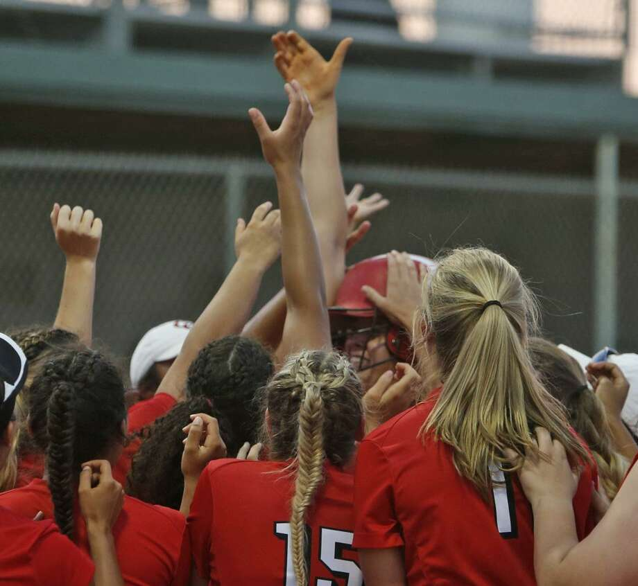 New Braunfels Canyon's Brooke Vestal is swarmed by teammates after her fourth inning HR in the Region IV-6A high school softball final between New Braunfels Canyon and Warren at Southwest High School on Friday, May 25, 2018. Photo: Ronald Cortes, For The San Antonio Express News / 2018 Ronald Cortes
