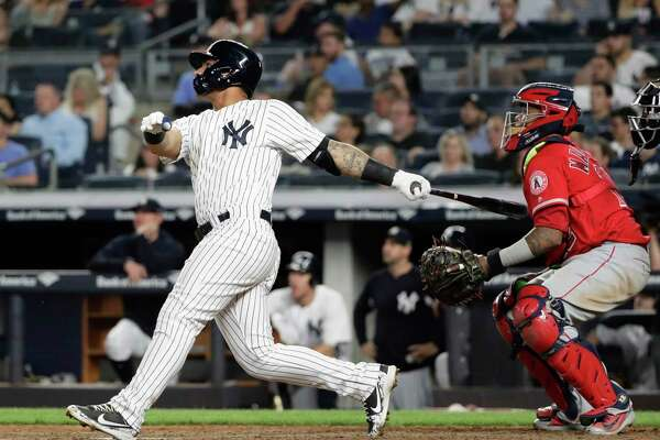 Los Angeles Angels catcher Martin Maldonado watches as New York Yankees' Gleyber Torres, left, follows through on a home run during the seventh inning of a baseball game Friday, May 25, 2018, in New York. (AP Photo/Frank Franklin II)