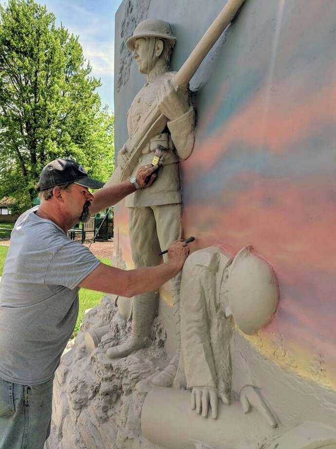 Artist Chris Moran of South Boardman works on painting and increasing definition on Beaverton's World War I monument, 'The Survivor,' on Thursday at Ross Lake Park. City officials are excited to give residents and others a sneak peek of the statue during the Memorial Day events. (Tereasa Nims/for the Daily News)