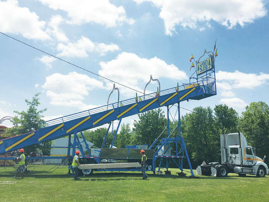 Workers set up the Land Slide, installing and doing daily inspections, preparing for the Italian-American Days Festival in Benld. Swyear Amusements Inc.'s trucks arrived in the city of Benld a week early to set up its 18 amusement rides. Photo:       Jill Moon| Hearst Newspapers