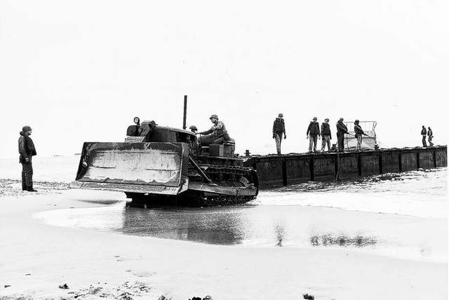 A Caterpillar track-type tractor moves onto the beach in France with U.S. troops during World War II. Photo:       Caterpillar Archives