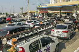 Vehicles sit in line to refuel Thursday in Sao Paulo, Brazil, where a truckers strike over rising fuel costs has halted deliveries and caused a shortage of goods and services throughout the country.