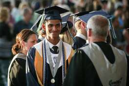 College Park students file into their seats during the College Park High School graduation on Friday, May 25, 2018, at the Cynthia Woods Mitchell Pavilion.