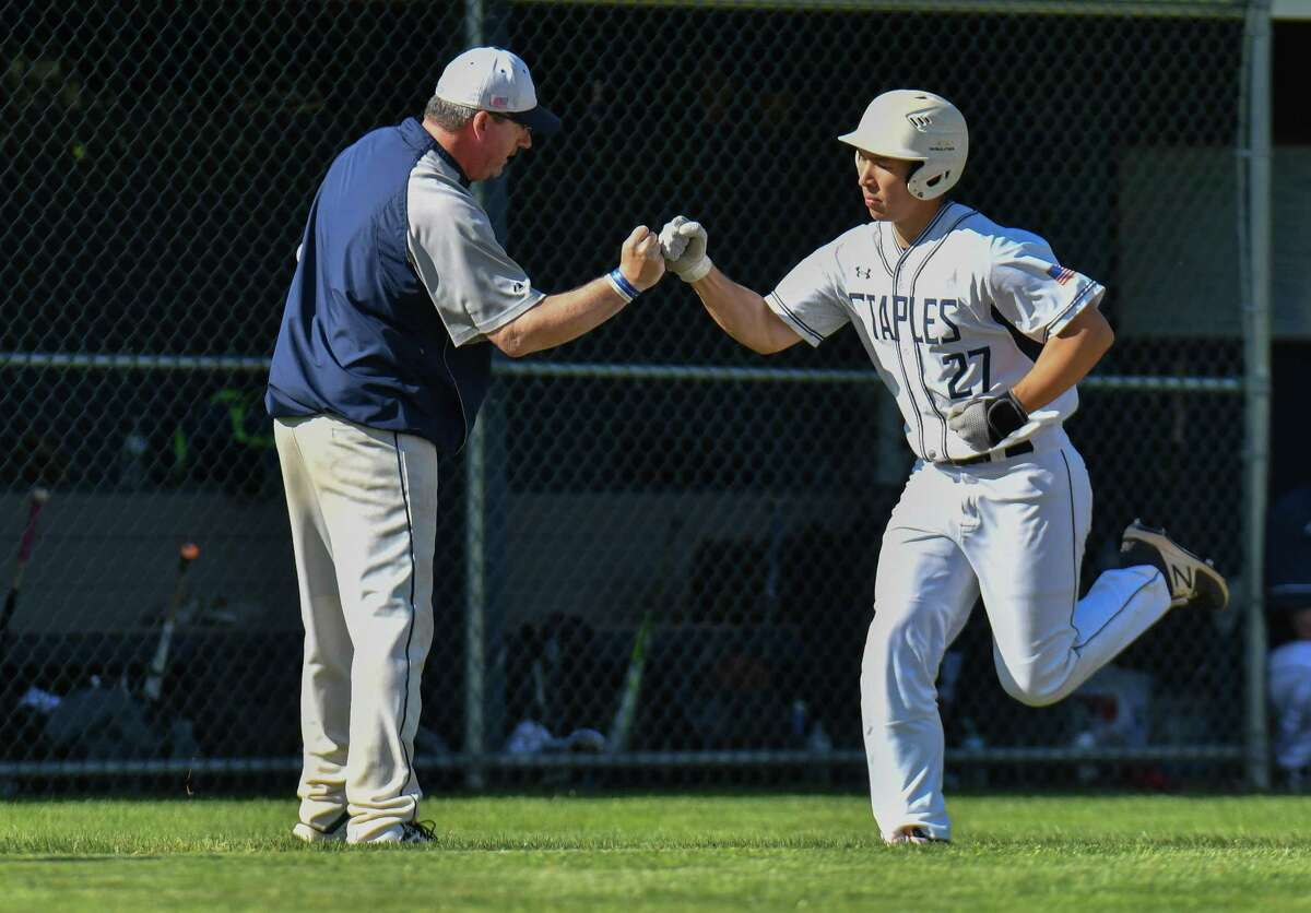 Staples' Chad Knight gets a high-five from coach Jack McFarland after hitting a two-run home run against Greenwich on May 21.