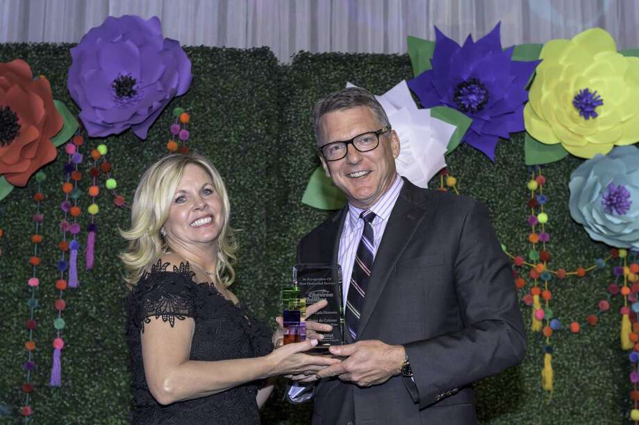 Habitat gala co-chair and board member Kim Lindley presented an award to Mark Lashier, CEO of Chevron Phillips Chemical Company, recognizing the company as the 2018 Habitat Gala honoree for their dedicated service to Habitat. Photo: Derrick Bryant Photography / Derrick Bryant Photography / DERRICK