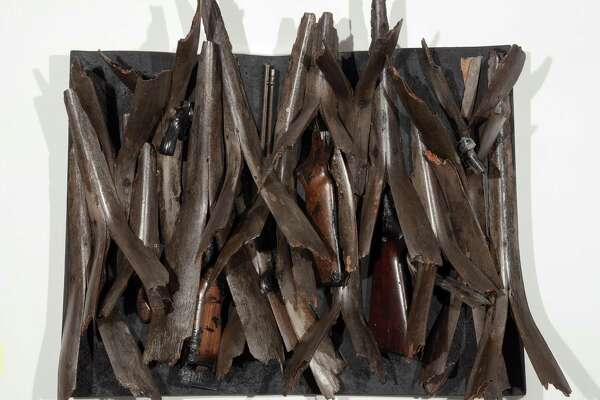 """Ron Bechet's """"Swords to Ploughshares,"""" made with palm fronds, gun parts and paint on wood panel."""