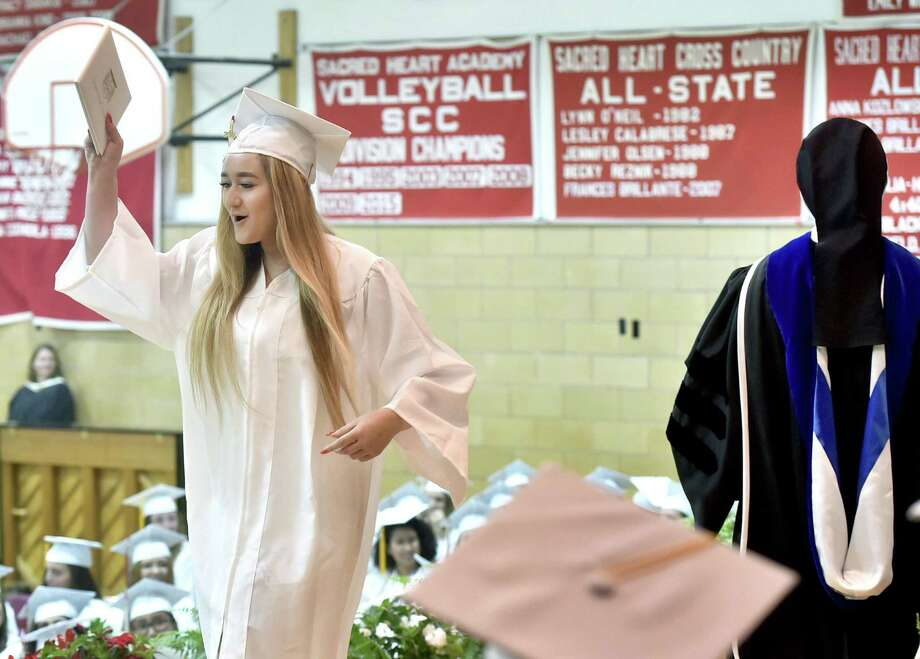 Hamden, Connecticut - May 26, 2018: Sacred Heart Academy graduate Kate Grieco of Guilford cheers as she receives diploma during the 2018 Commencement Exercises Saturday morning at SHA in Hamden. Photo: Peter Hvizdak / Hearst Connecticut Media / New Haven Register