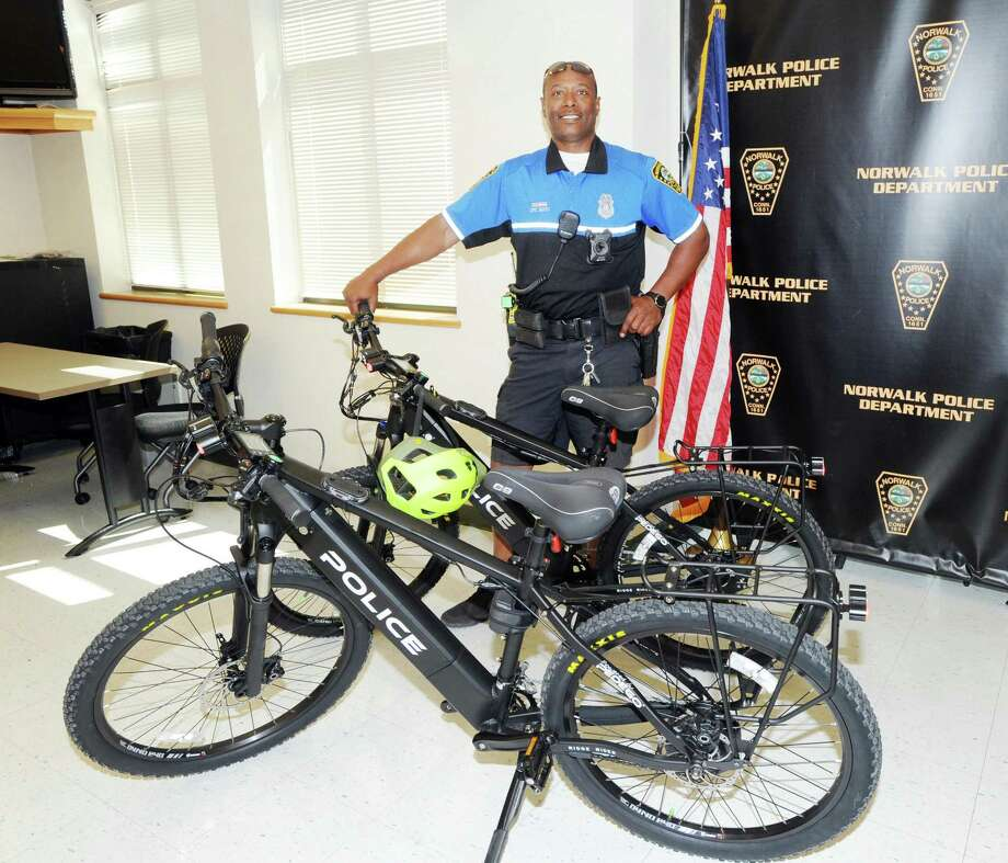Norwalk Police officer Max Sixto poses with two Pedego electric bikes that were donated to the Norwalk Police Department in a collaboration by Norwalk agencies at Norwalk Police Department Headquarters, Conn., Friday, May 25, 2018. Photo: Bob Luckey Jr. / Hearst Connecticut Media / Greenwich Time