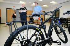 Norwalk Police Chief Thomas Kulhawik, left, speaks with Mike Heslin, right, of Pedego Electric Bikes during a press conference announcing the donation of two electric bikes to the Norwalk Police Department in a collaboration by Norwalk agencies at Norwalk Police Department Headquarters, Conn., Friday, May 25, 2018. Heslin's Pedego Electric Bike Dealership is located in Norwalk and was the supplier of the bikes.