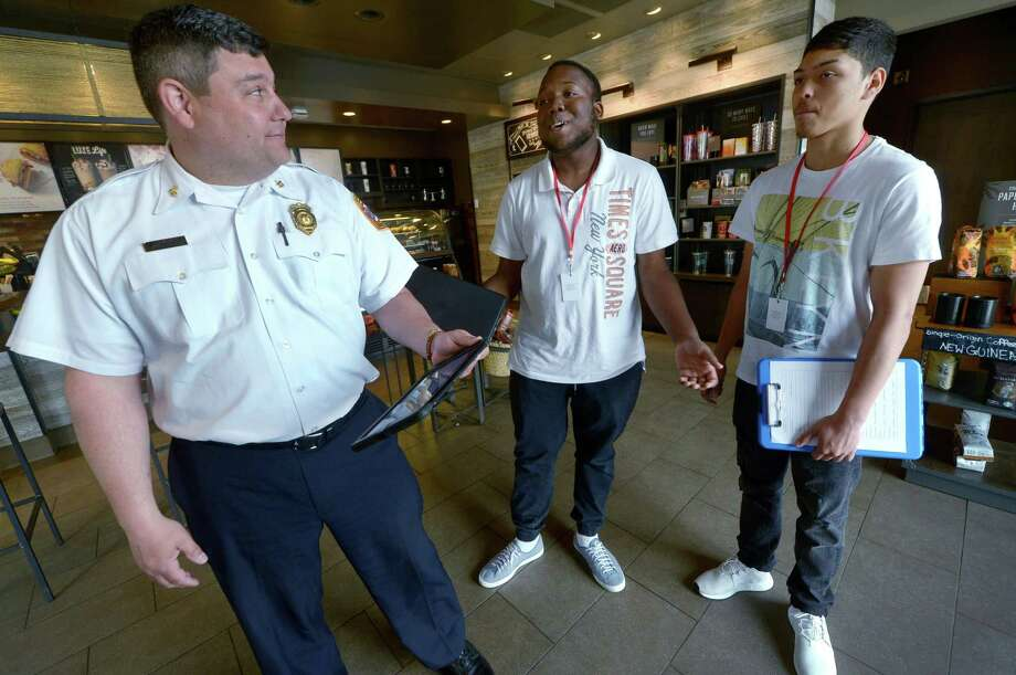 Deputy Fire Chief Al Bassett accompanies Brien McMahon High School students Malik Scott and Johan Mena while assisting with pre-fire planning survey at establishments in Darinor Plaza Tuesday, May 22, 2018, as the students begin their four week internship at the Norwalk Fire Department. Photo: Erik Trautmann / Hearst Connecticut Media / Norwalk Hour