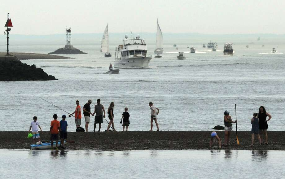 Beachgoers watch the boats in Norwalk Harbor as they visit Calf Pasture Beach for the Memorial Day weekend Saturday, May 26, 2018, in Norwalk, Conn. Photo: Erik Trautmann / Hearst Connecticut Media / Norwalk Hour