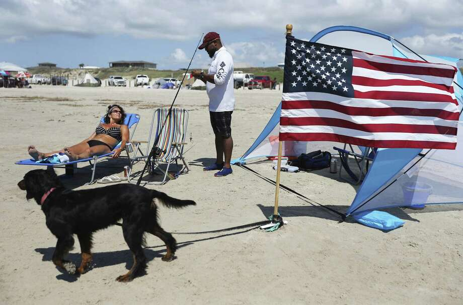 Duane Bailey of San Antonio resets a fishing line as girlfriend Susan Heckaman from Austin soaks in the sun on a beach in Port Aransas on Saturday, May 26, 2018. Bailey, a Marine veteran, said he makes the trip to the coast to fish and to also help support the local economy recover from Hurricane Harvey. Bailey, like some San Antonio residents, made the three-hour trek to Port Aransas to celebrate Memorial Day weekend. Since Hurricane Harvey struck the area last year, the city and business owners have been racing to recover from the devastating storm and draw tourists back to the tiny island town. City Mayor Charles R. Bujan said despite perfect conditions for the beaches and nearly all restaurants have reopened, accommodations for visitors is still only at about half of usual capacity. (Kin Man Hui/San Antonio Express-News) Photo: Kin Man Hui, Staff / San Antonio Express-News / ©2018 San Antonio Express-News