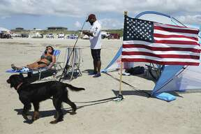 Duane Bailey of San Antonio resets a fishing line as girlfriend Susan Heckaman from Austin soaks in the sun on a beach in Port Aransas on Saturday, May 26, 2018. Bailey, a Marine veteran, said he makes the trip to the coast to fish and to also help support the local economy recover from Hurricane Harvey. Bailey, like some San Antonio residents, made the three-hour trek to Port Aransas to celebrate Memorial Day weekend. Since Hurricane Harvey struck the area last year, the city and business owners have been racing to recover from the devastating storm and draw tourists back to the tiny island town. City Mayor Charles R. Bujan said despite perfect conditions for the beaches and nearly all restaurants have reopened, accommodations for visitors is still only at about half of usual capacity. (Kin Man Hui/San Antonio Express-News)