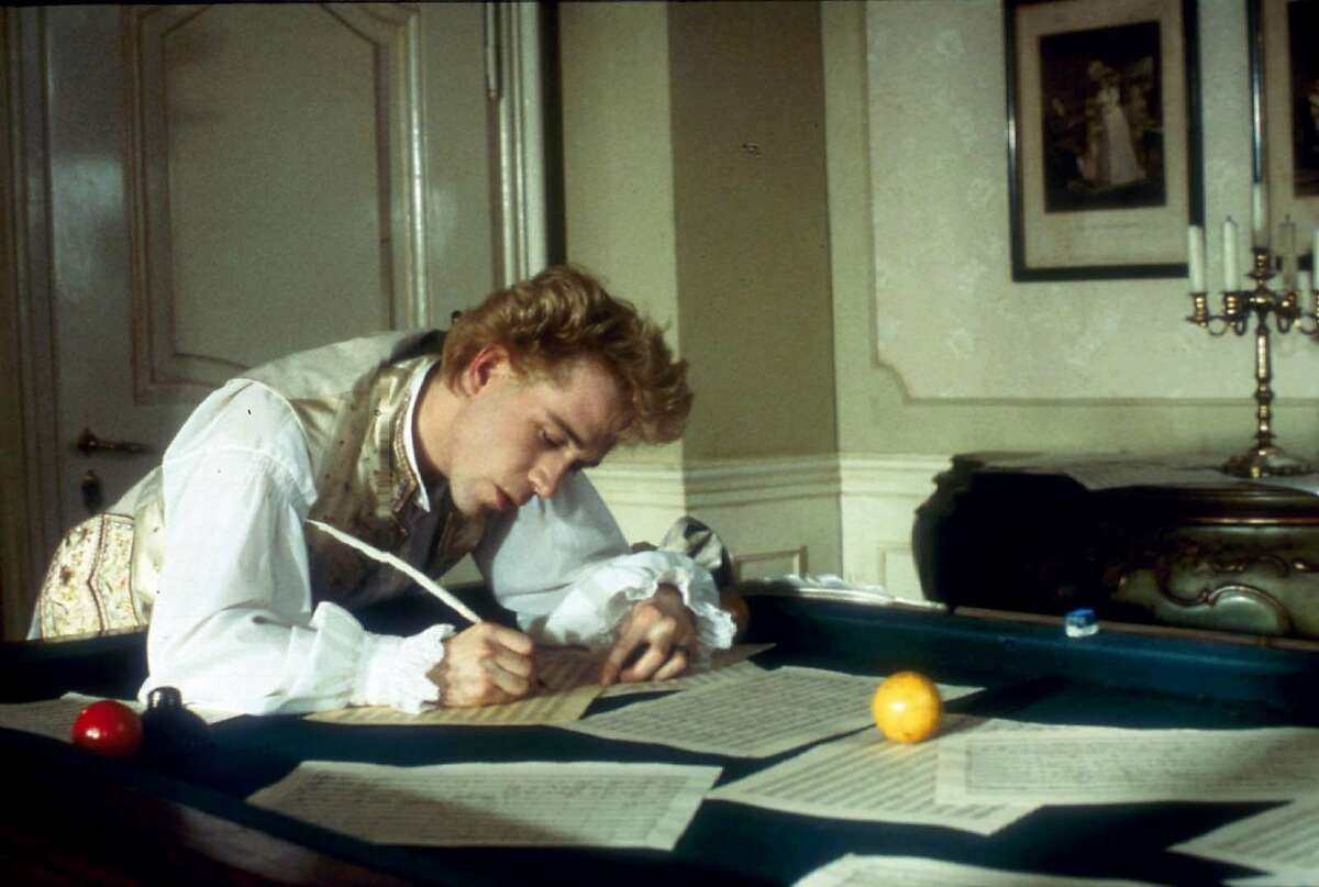 """ADVANCE FOR WEEKEND EDITIONS APRIL 4-7 -- Mozart (Tom Hulce) composes music over a billiard table in the """"Amadeus Director's Cut."""" (AP Photo/Saul Zaentz Company)"""