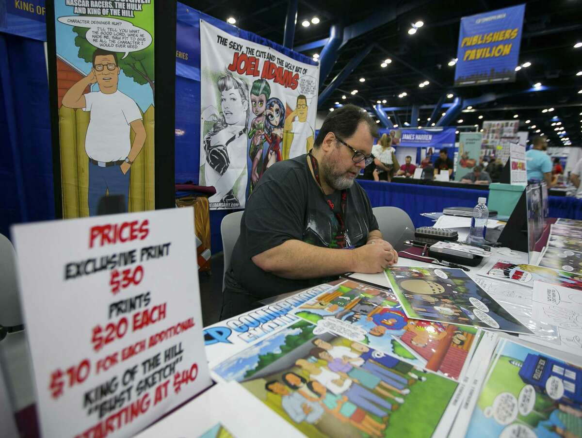 Illustrator Joel Adams signs prints at Comicpalooza on Saturday, May 26, 2018. (Annie Mulligan / For the Houston Chronicle)