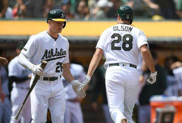 OAKLAND, CA - MAY 26:  Matt Olson #28 of the Oakland Athletics is congratulated by Matt Chapman #26 after Olson hit a solo home run against the Arizona Diamondbacks in the bottom of the seventh inning at the Oakland Alameda Coliseum on May 26, 2018 in Oakland, California.  (Photo by Thearon W. Henderson/Getty Images)
