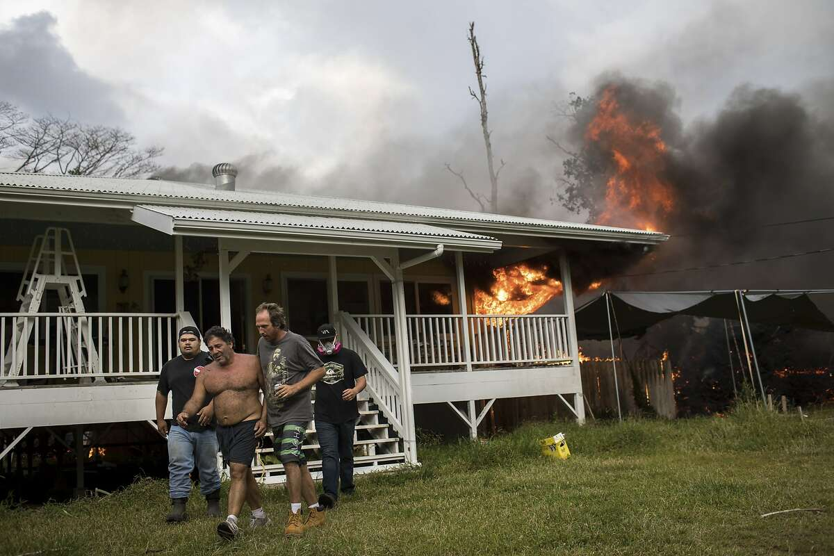 Emanuel Roditis, second from left, is led out of his burning house as lava from the Kilauea volcano advances through his property in Pahoa, Hawaii, May 25, 2018. The growing ferocity this month of Kilauea's eruptions, which are burying home after home under rivers of molten rock, has provoked questions about how thousands of families managed to put down stakes in such a disaster-prone domain in the first place. (Tamir Kalifa/The New York Times)
