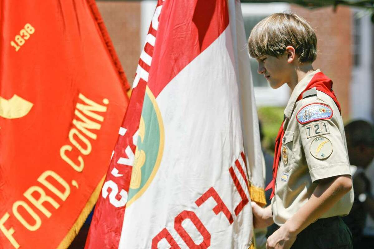 Clayton Simses of Boy Scout troop 721 stands with the troop's flag on the Milford Green on Sunday, July 4, 2010 during a bell-ringing ceremony honoring the signing of the Declaration of Independence.