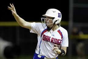 Oak Ridge courtesy runner Lauren Hastings motions toward the ball as Autumn Sydlik hits a two-run, walk-off home run in the ninth inning of Game 2 during a Region II-6A final on Saturday, May 26, 2018, in Tomball. Oak Ridge defeated Klein Collins 8-6 to advance to next week's state tournament.