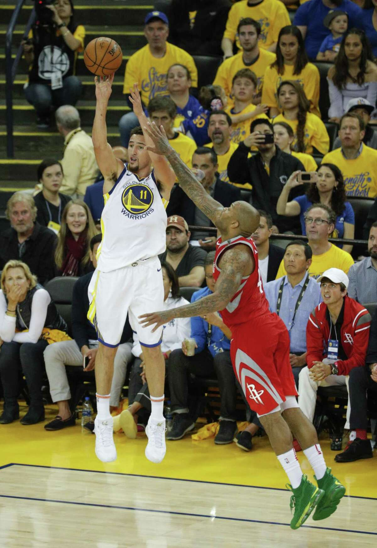Golden State Warriors' Klay Thompson shoots a three-pointer over Houston Rockets' PJ Tucker in the third quarter during game 6 of the Western Conference Finals between the Golden State Warriors and the Houston Rockets at Oracle Arena on Saturday, May 26, 2018 in Oakland, Calif.
