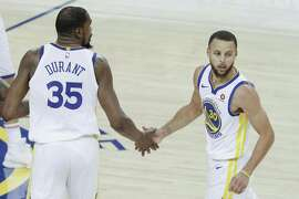 Golden State Warriors' Kevin Durant and Stephen Curry touch hands in the third quarter during game 6 of the Western Conference Finals between the Golden State Warriors and the Houston Rockets at Oracle Arena on Saturday, May 26, 2018 in Oakland, Calif.