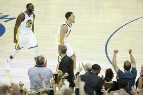 Golden State Warriors' Draymond Green and Klay Thompson react after Thompson hit a three-pointer in the fourth quarter during game 6 of the Western Conference Finals between the Golden State Warriors and the Houston Rockets at Oracle Arena on Saturday, May 26, 2018 in Oakland, Calif.