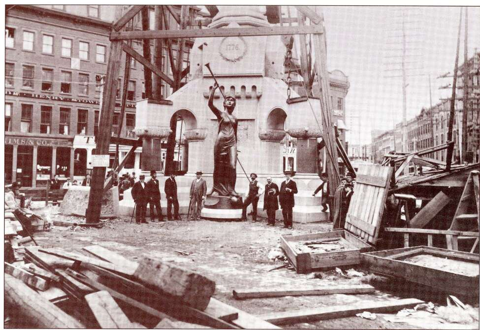 The Call to Arms statue on the ground and the open crates with the bronze reliefs plaques in Monument Square during construction of the Rensselaer County Soldiers and Sailors Monument.   Collection Rensselaer  County Historical Society, Troy, NY