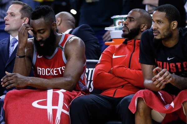 Houston Rockets guard James Harden, left,   guard Chris Paul, center, and forward Trevor Ariza sit on the bench during the fourth quarter of Game 6 of the NBA Western Conference Finals against the Golden State Warriors at Oracle Arena, Saturday, May 26, 2018, in Oakland.