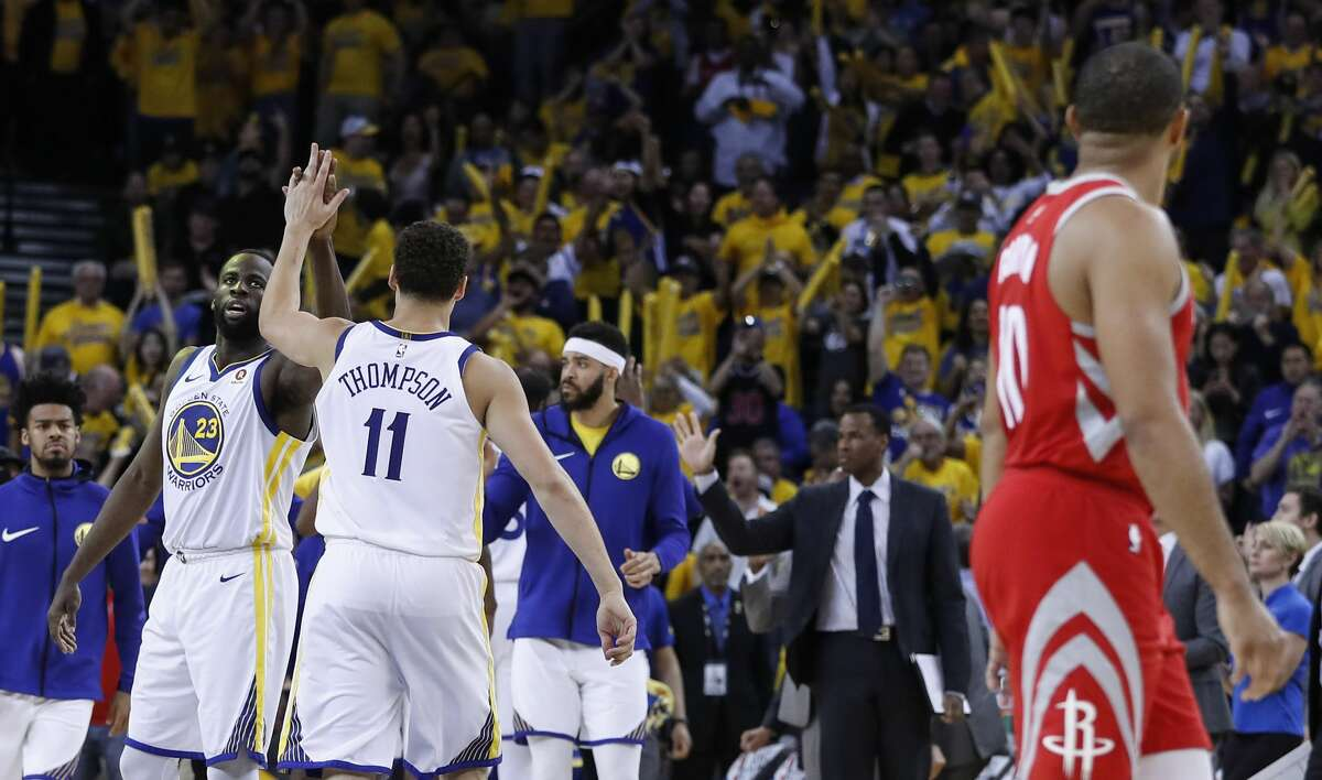 Golden State Warriors forward Draymond Green (23) and guard Klay Thompson (11) high five as they leave the court during a time out against the Houston Rockets during the second half of Game 6 of the NBA Western Conference Finals at Oracle Arena, Saturday, May 26, 2018, in Oakland. ( Karen Warren / Houston Chronicle )