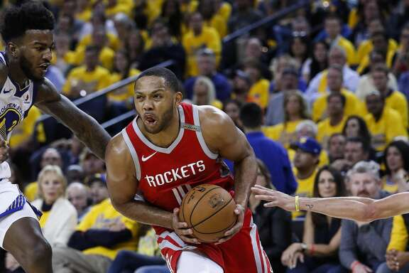 Houston Rockets guard Eric Gordon (10) takes the ball between Golden State Warriors center Jordan Bell (2) and guard Stephen Curry (30) during the first half of Game 6 of the NBA Western Conference Finals at Oracle Arena, Saturday, May 26, 2018, in Oakland.  ( Karen Warren  / Houston Chronicle )