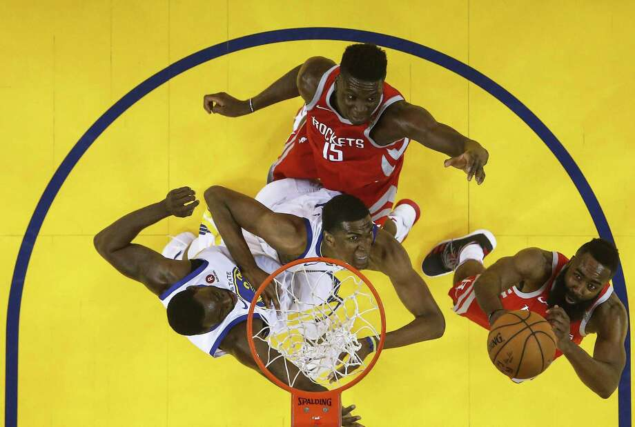 Houston Rockets center Clint Capela (15) battes under the basket against Golden State Warriors forwards Draymond Green (23) and Kevon Looney (5) as James Harden rebounds during the first half of Game 6 of the NBA Western Conference Finals at Oracle Arena, Saturday, May 26, 2018, in Oakland.  ( Karen Warren  / Houston Chronicle ) Photo: Karen Warren, Staff / Houston Chronicle / © 2018 Houston Chronicle