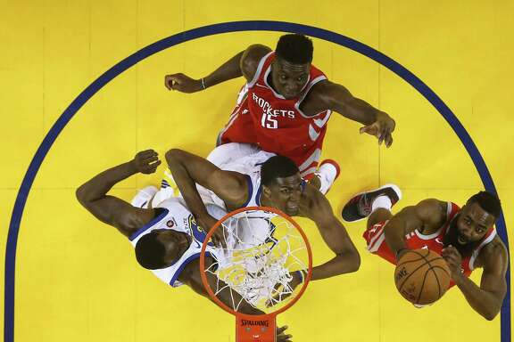 Houston Rockets center Clint Capela (15) battes under the basket against Golden State Warriors forwards Draymond Green (23) and Kevon Looney (5) as James Harden rebounds during the first half of Game 6 of the NBA Western Conference Finals at Oracle Arena, Saturday, May 26, 2018, in Oakland.  ( Karen Warren  / Houston Chronicle )