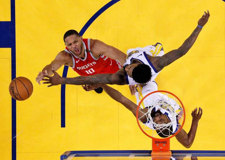 Eric Gordon (10) drives to the basket defended by Jordan Bell (2) and Kevin Durant (35) in the second half as the Golden State Warriors played the Houston Rockets in Game 6 of the Western Conference Finals at Oracle Arena in Oakland, Calif., on Sunday, May 27, 2018.