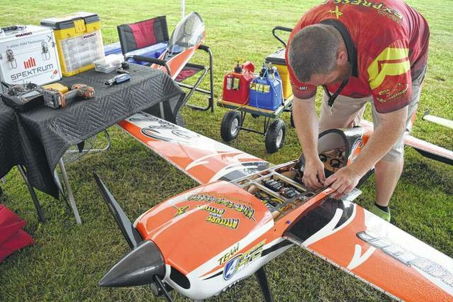 Ryan Mowery of Granite City installs batteries in his Slick 540 aerobatic model airplane Saturday at the Jacksonville Propkickers' Fly-In south of Jacksonville. Photo:       Greg Olson | Journal-Courier