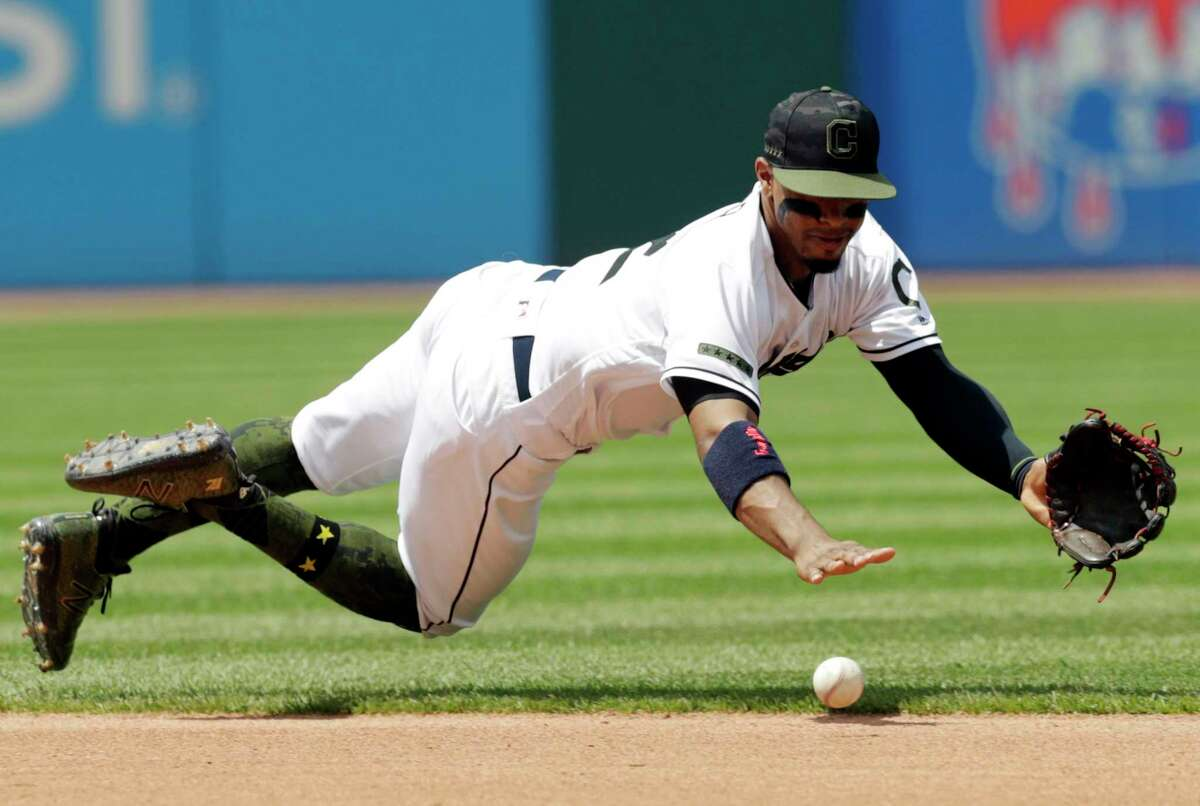 Cleveland Indians' Francisco Lindor dives for a ball hit by Houston Astros' Jose Altuve in the fourth inning of a baseball game Sunday, May 27, 2018, in Cleveland. Altuve was safe at first base on the play. (AP Photo/Tony Dejak)