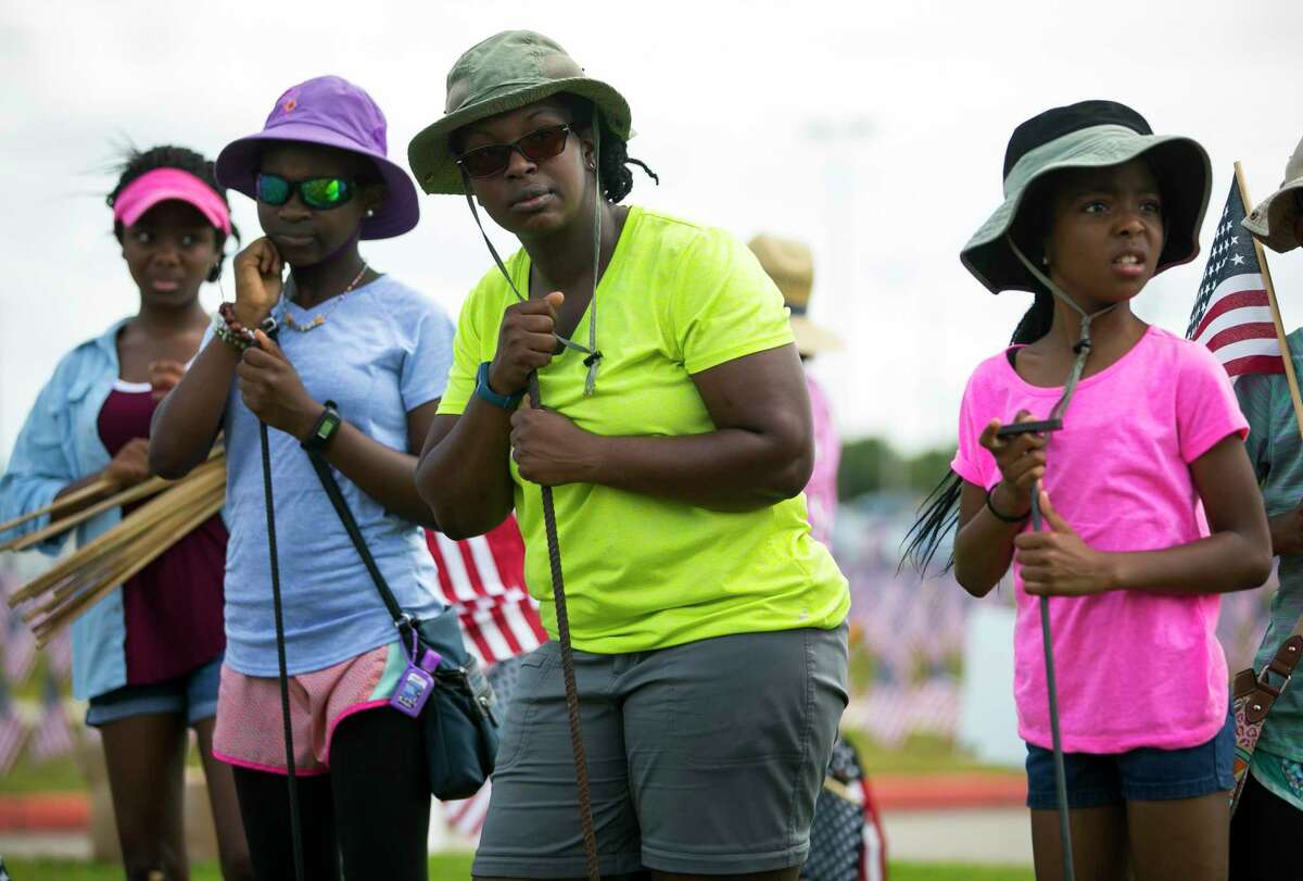 Raquel Lewis, center, volunteers with her two daughters and two nieces to place 38,000 American flags on the grounds of Sagemont Church on Saturday, May 26, 2018.