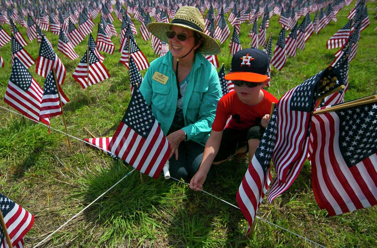Diane Burcham works with her eight-year-old grandson, Bennett, place 38,000 American flags with both community and church members on the grounds of Sagemont Church on Saturday, May 26, 2018.