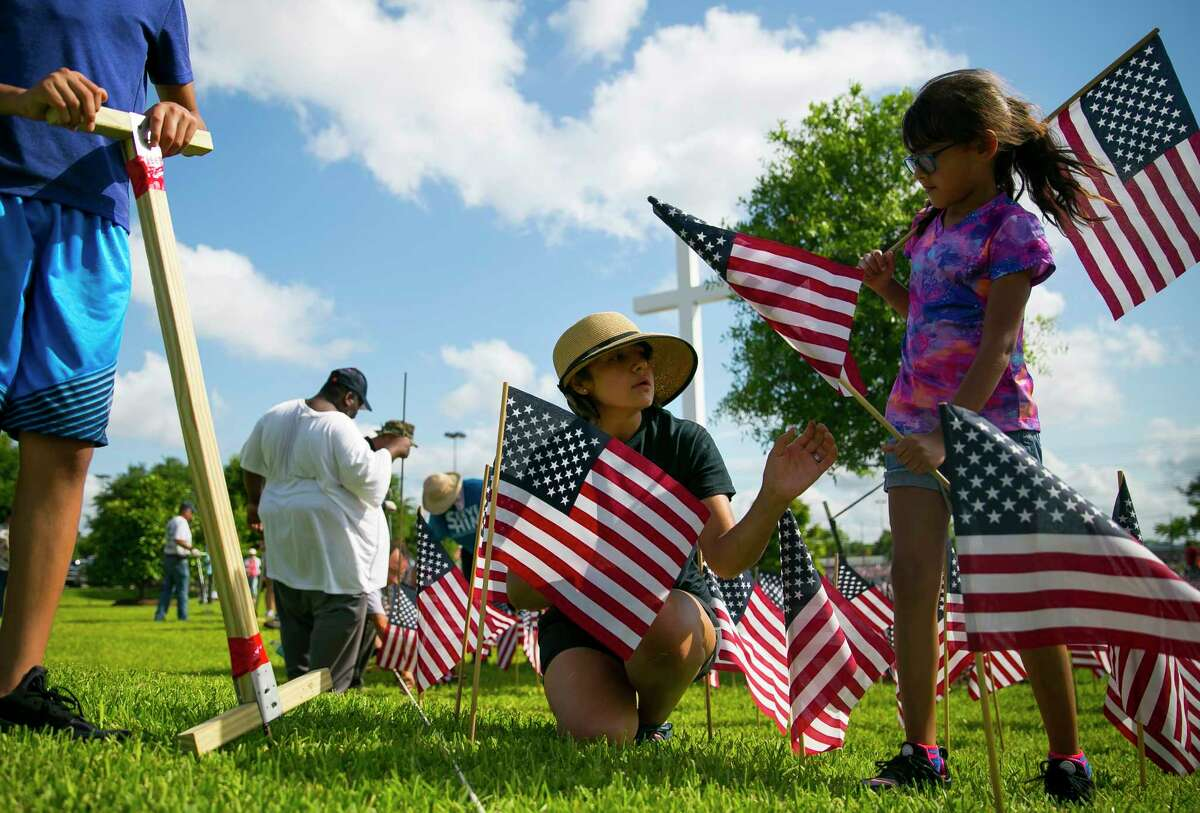 Pearland resident Josie Aguirre, center, receives a flag from her seven-year-old daughter, Jennifer, as they help place 38,000 American flags on the grounds of Sagemont Church on Saturday, May 26, 2018. Aguirre brought both her daughter and 12-year-old son, Jacob, to join church and community members to memorialize Texas who were killed in war.