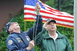 Byram veterans Thomas Curtin, left, and Don Merchant participate in the flag-raising at the annual Byram Veterans Association Memorial Day Parade in the Byram section of Greenwich, Conn. Sunday, May 27, 2018. Members of the Byram Veterans marched through the streets with town leaders before a small ceremony of remembrance and honor in front of the Byram Shubert Library.