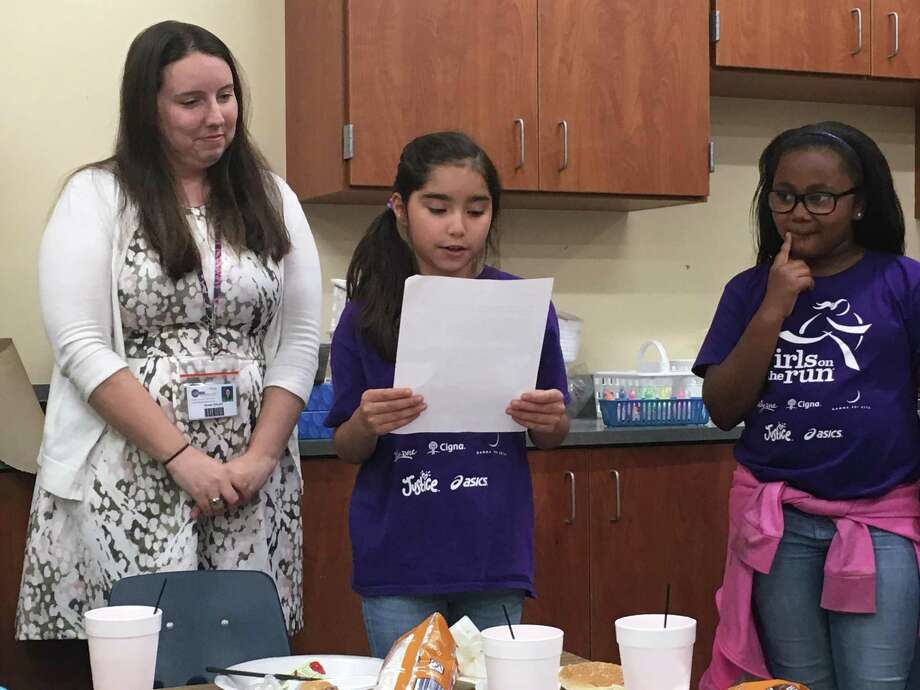 A student from Runyan Elementary School's Girls on the Run program reads a letter she wrote thanking the Rotary Club of Conroe for their support of the school's Girls on the Run program. The club held their annual lunch at the school on May 22. Photo: Courtesy Photo / Courtesy Photo