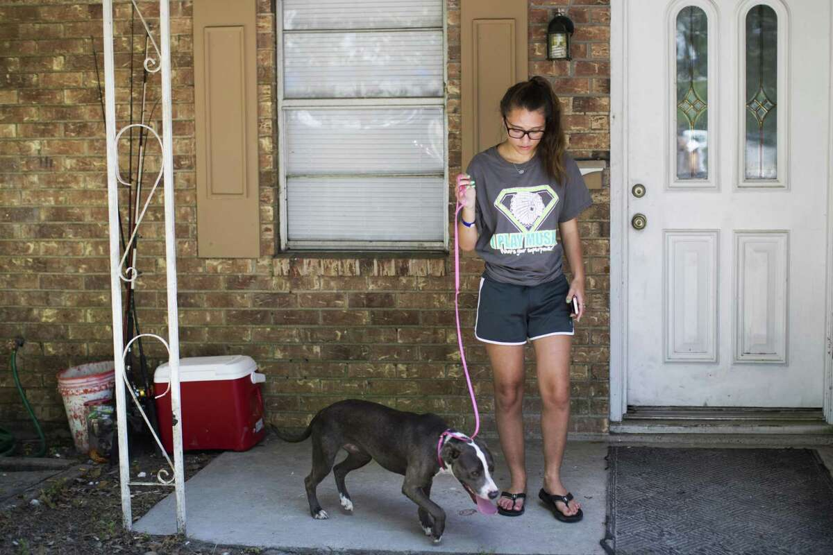 Santa Fe High School student Brianna Huston, 15, walks her dog Gracie on May 22, 2018, at her home in Santa Fe not too far from the high school, where a mass shooting occurred May 18.