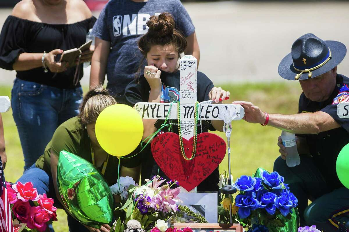 A young woman cries Tuesday, May 22, 2018, by the memorial of Santa Fe High School freshman Aaron Kyle McLeod, who was among 10 people killed during a mass shooting at the school on May 18.