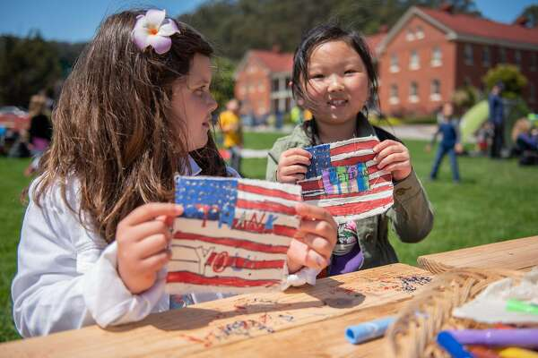 Sophie Philhour, 8 (left) and Addison Kim, 7, display their flags for the Presidio Trust�s Civilian Veteran Flag Collage on Sunday, May 27, 2018.