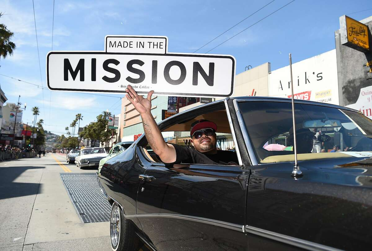 Fernando Sanchez holds up a sign in the Carnaval parade as it travels through the mission district of San Francisco on Sunday, May 27, 2018.