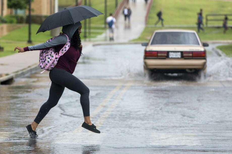 A UTSA student hops through puddles as she makes her way across the main campus in a September 2017 photo. UTSA has received a $1 million grant to install and study features to slow storm water runoff and improve water quality. Photo: William Luther /San Antonio Express-News / © 2017 San Antonio Express-News
