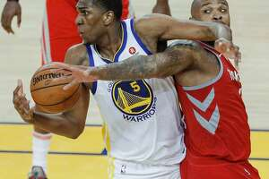 Golden State Warriors' Kevon Looney pulls down a rebound over Houston Rockets' Eric Gordon in the third quarter during game 6 of the Western Conference Finals between the Golden State Warriors and the Houston Rockets at Oracle Arena on Saturday, May 26, 2018 in Oakland, Calif.