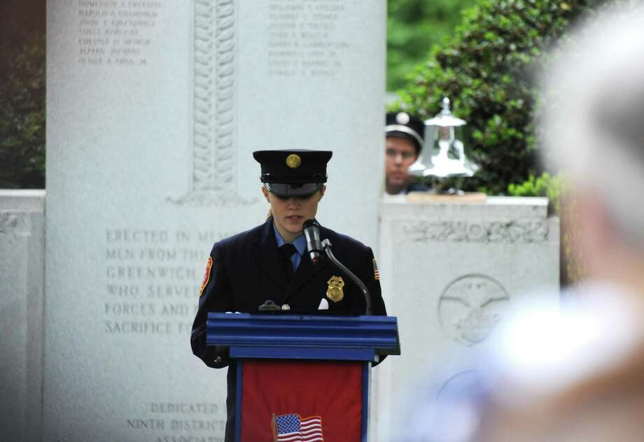 Glenville volunteer firefighter Karlie Darmocal reads the names of local residents who gave their lives in battle at the Ninth District Veterans Association and the Glenville Volunteer Fire Company's annual Glenville Parade and Memorial Service in the Glenville section of Greenwich, Conn. Sunday, May 27, 2018. The parade route ran the length of Glenville Street with a wreath-laying ceremony at the monument adjacent to the Glenville Fire House on Glenville Road. A reception hosted by the Glenville Volunteer Fire Company followed the parade and memorial service. Photo: Tyler Sizemore / Hearst Connecticut Media / Greenwich Time