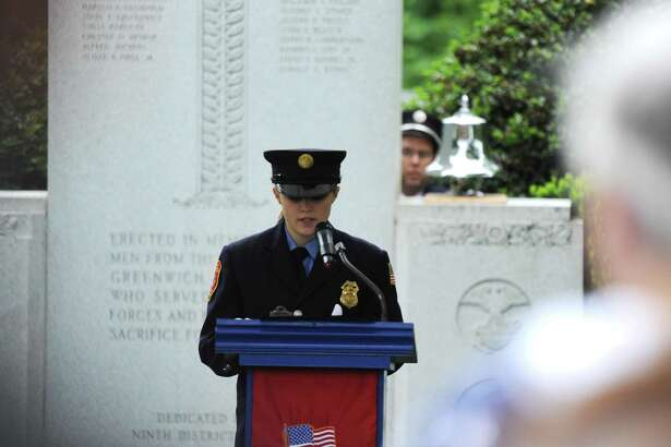 Glenville volunteer firefighter Karlie Darmocal reads the names of local residents who gave their lives in battle at the Ninth District Veterans Association and the Glenville Volunteer Fire Company's annual Glenville Parade and Memorial Service in the Glenville section of Greenwich, Conn. Sunday, May 27, 2018. The parade route ran the length of Glenville Street with a wreath-laying ceremony at the monument adjacent to the Glenville Fire House on Glenville Road. A reception hosted by the Glenville Volunteer Fire Company followed the parade and memorial service.